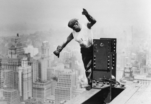 construction worker walking the beam high above city