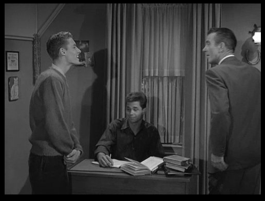 Eddie Haskell talking to Ward Cleaver Wally sitting at desk