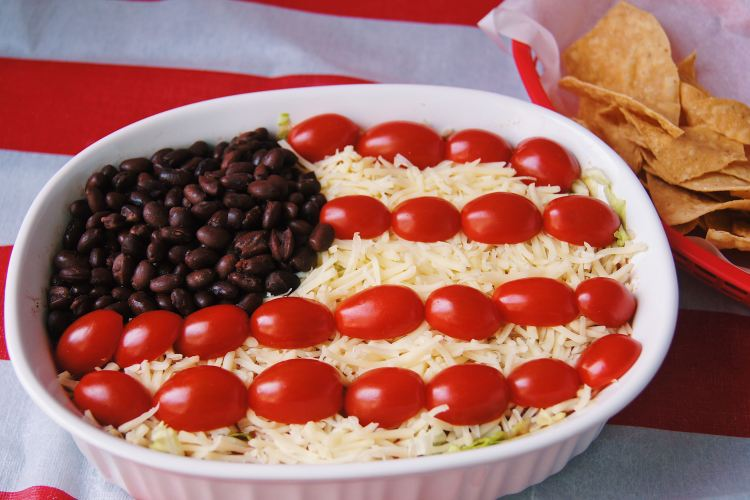 7 layer flag dip in a white casserole dish with chips