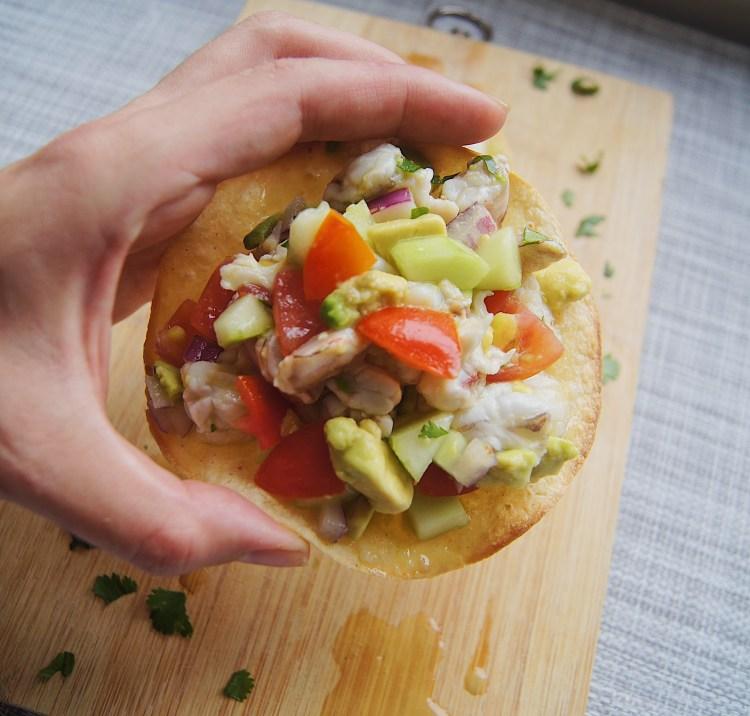 Ceviche hand holding tostada