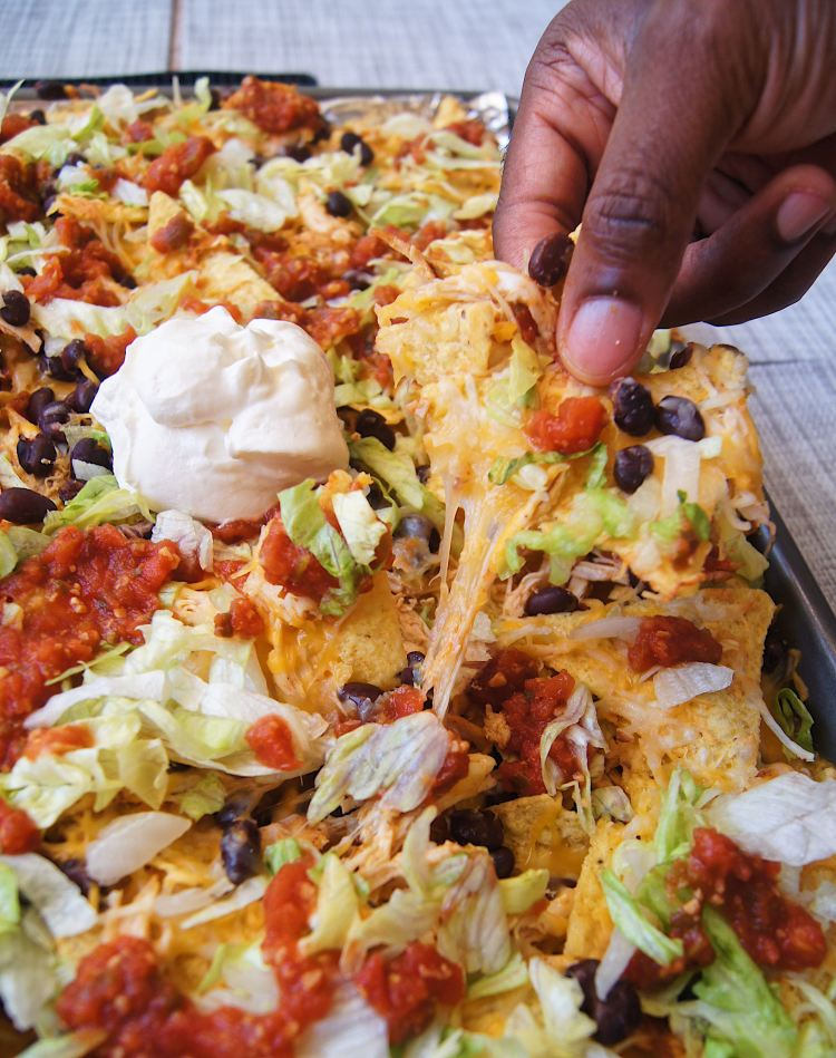 Sheet-Pan-Chicken-Nachos-with-hand-holding-a-chip
