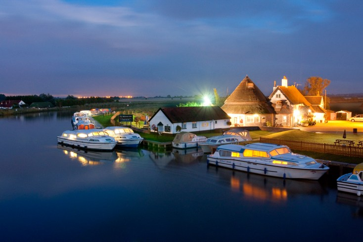 Boats moored outside a pub and restaurant at Acle Bridge on the Norfolk Broads