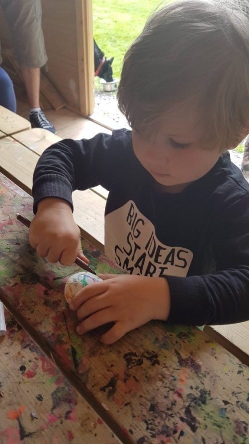 A small child painting rocks