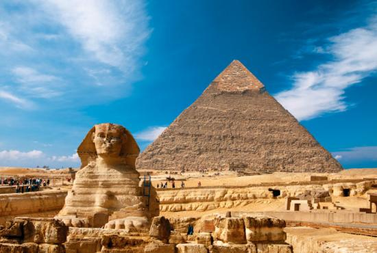 The Sphinx and Great Pyramid of Giza in front of a bright blue sky