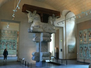 visitor looks us at Bull Headed stone capital from Darius' Winter Palace, Susa, Iran 6th Century BC. In the Louvre Paris