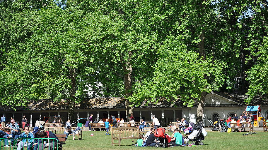 families with kids sat under trees near play park at Coram's Fields