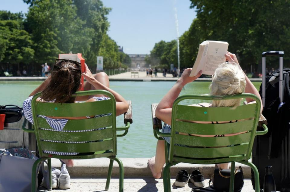 Two women reading on green chairs in Paris