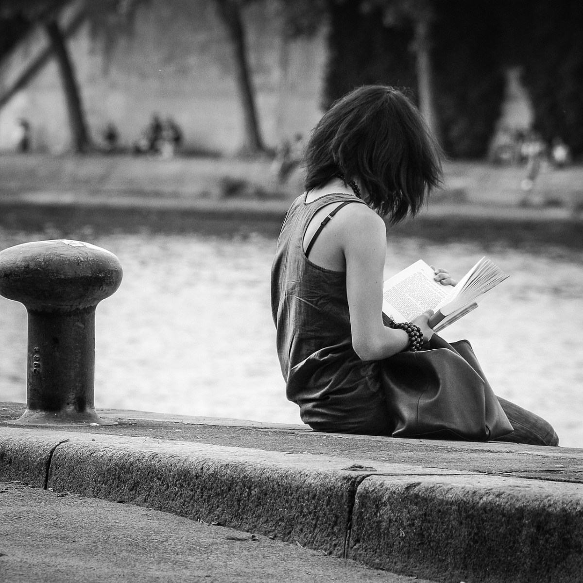 A woman reading by the Seine in Paris