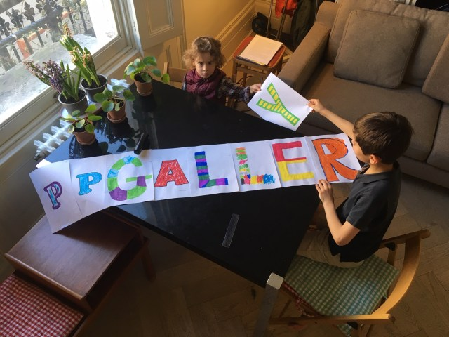 "Two children hold a home-made sign saying ""PP Gallery"", part of their homeschool art project"