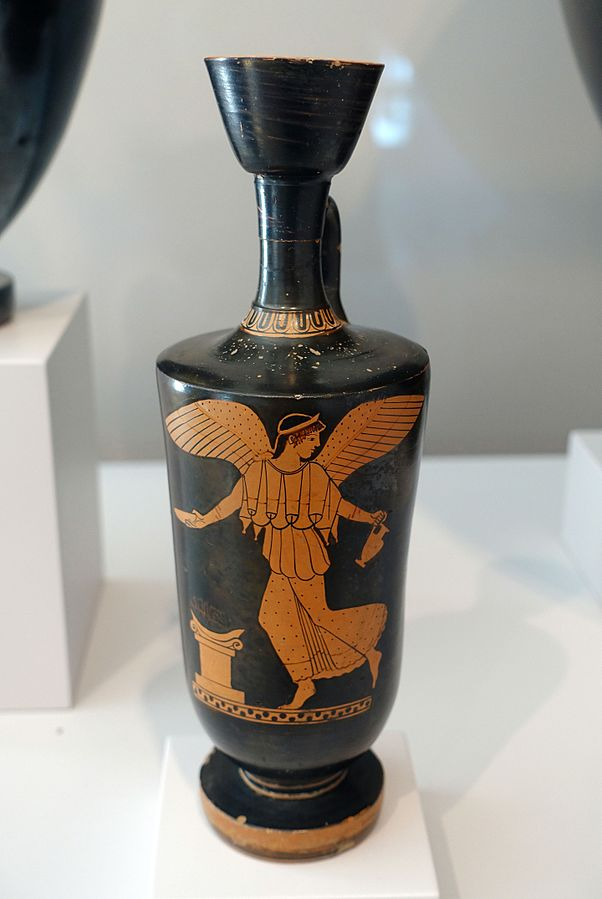 Red image on black vase of the Goddess of Victory pouring a libation.