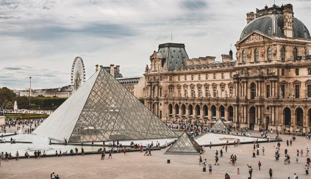 The large courtyard at the Louvre Museum on a busy day. Three glass pyramids are visible, as well as the exterior of the Richelieu wing.