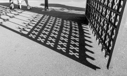 The shadow of an open wrought iron gate falls on the ground