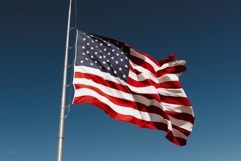 Photo of the American flag blowing in the breeze against a blue sky.