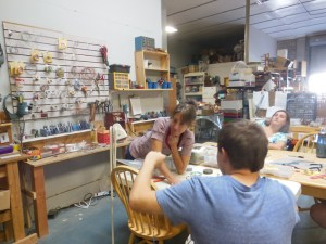 Mary Ann LaRoche of SEEDs for Autism works with a student in her warehouse which has many projects going simultaneously