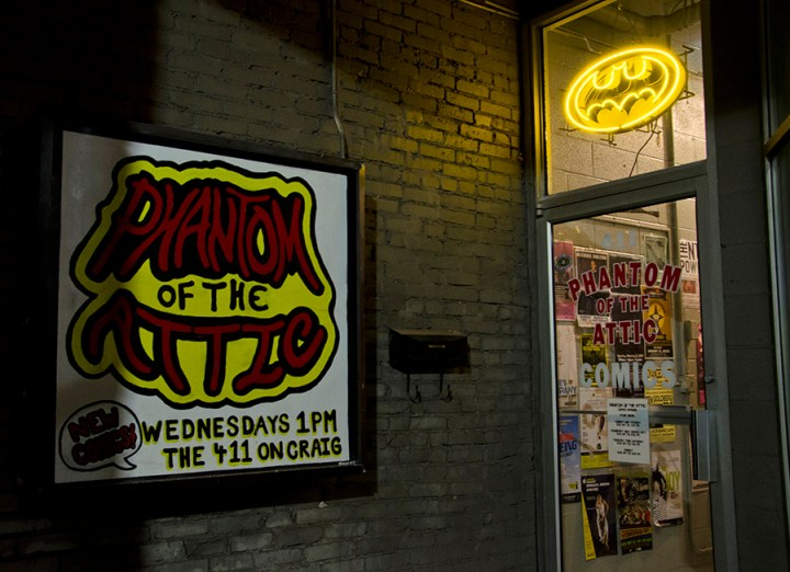 A Batman light shines the way into Phantom of the Attic Comics.