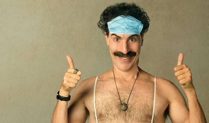 sacha baron cohen as borat shirtless wearing facemask on head and giving two thumbs up