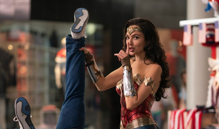 "Gal Gadot as Wonder Woman holding a man upside down by the leg while making the ""shhh"" hand gesture"