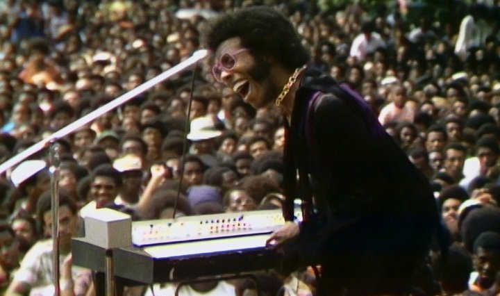 Sly of Sly and the Family Stone sings into a microphone in front of a crowd