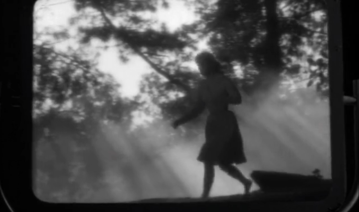 A woman in silhouette runs through a forest on a TV screen, black and white