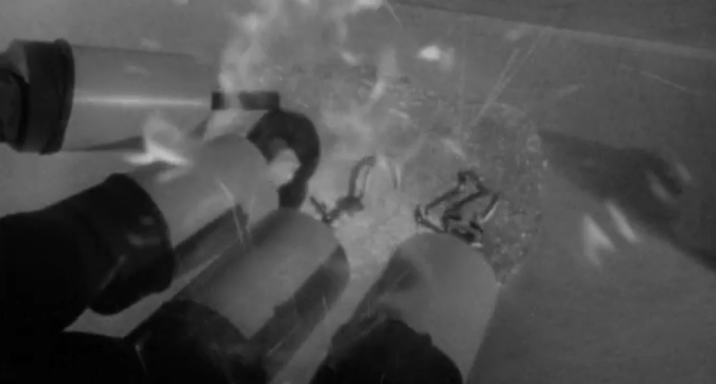 Scientists in protective suits and metal claws interact with a sparking radioactive experiment in a nuclear reactor
