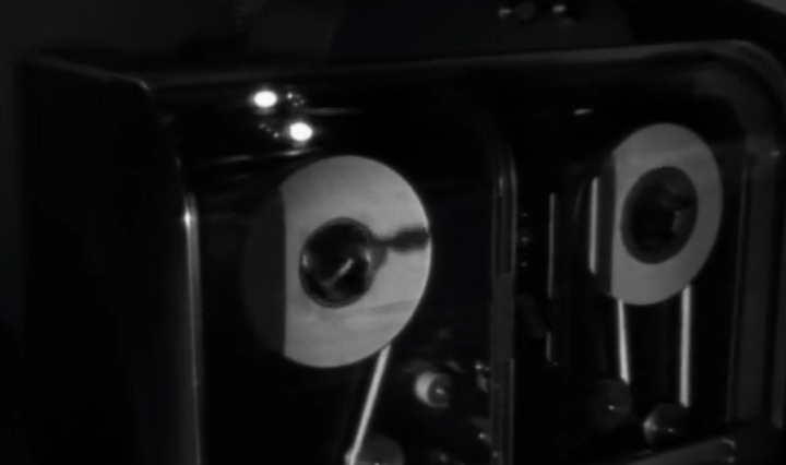 A large tape reel plays in a laboratory, black and white
