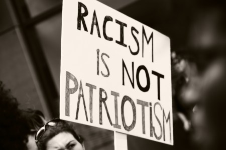 "A photo of a woman holding up a placard with the words ""Racism is not patriotism"" written on it."