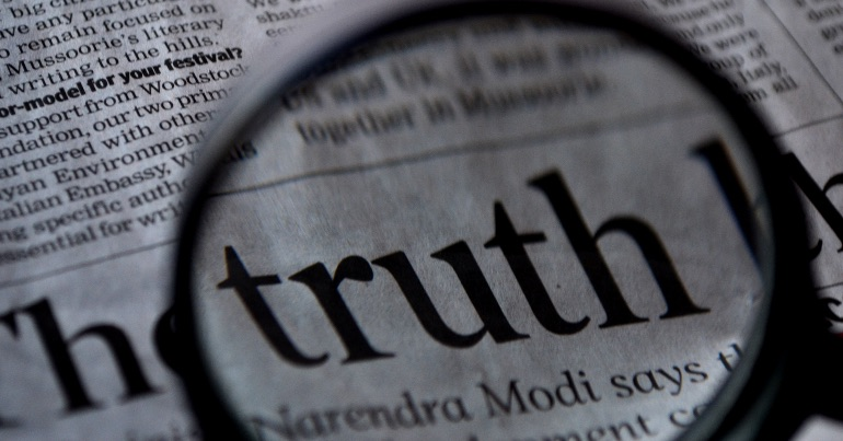 "A photo of a newspaper with the word ""truth"" magnified, highlighting the fact that reporting of truth by the media is important given that we live in a post-truth society."