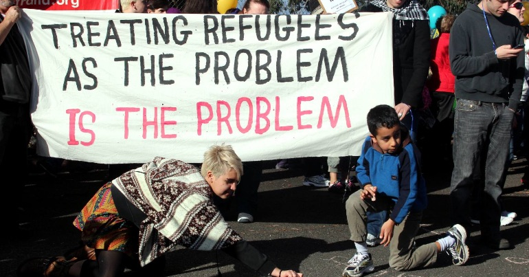 "A photo of demonstrators holding up a banner that says ""Treating refugees as the problem is the problem""."