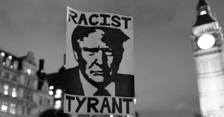 "A photo of a placard with Donald Trump's face on it with the words ""Racist"" and ""Tyrant"" on either side of his head, something which Alexis de Tocquville could have predicted 200 years ago."