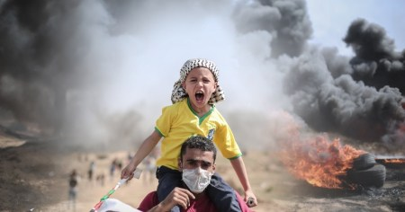 A photo of a Palestinian man carrying a child on his back after Israel's attack on the Gaza Strip last year.
