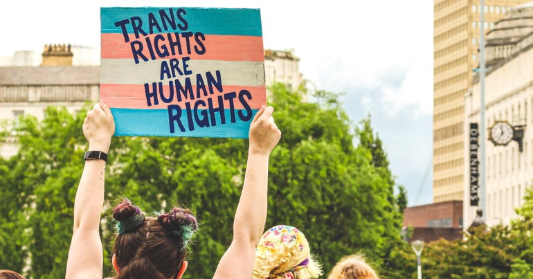 """A photo of a person holding a banner which reads """"Trans rights are human rights""""."""