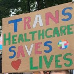 A photo of a placard that reads Trans Healthcare Saves Lives, which a protestor held at a rally to draw attention to the lack of proper healthcare for trans people in Ireland.