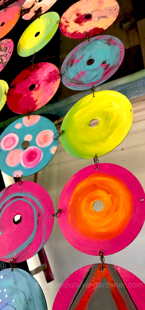 Upcycled DVDs and CDs -- painted and wired into wall hanging