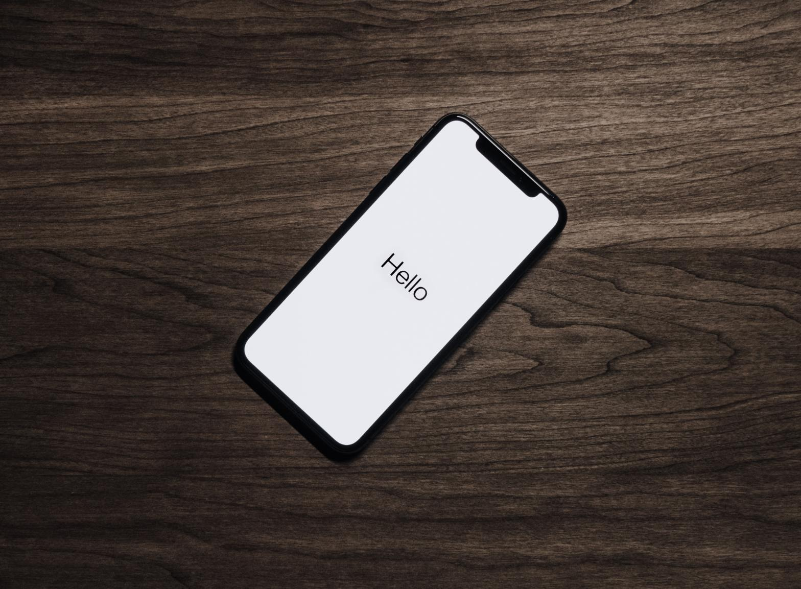 "image of iphone on table with the word ""hello"" displayed on the screen"