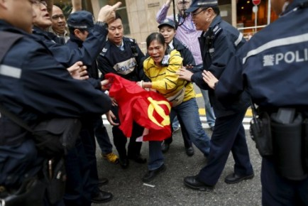 A demonstrator clashes with police officers as she attempts to place a flag of the Communist Party of China on the ground and step over it during a protest over the disappearance of booksellers, in Hong Kong, China January 10, 2016. REUTERS/Tyrone Siu
