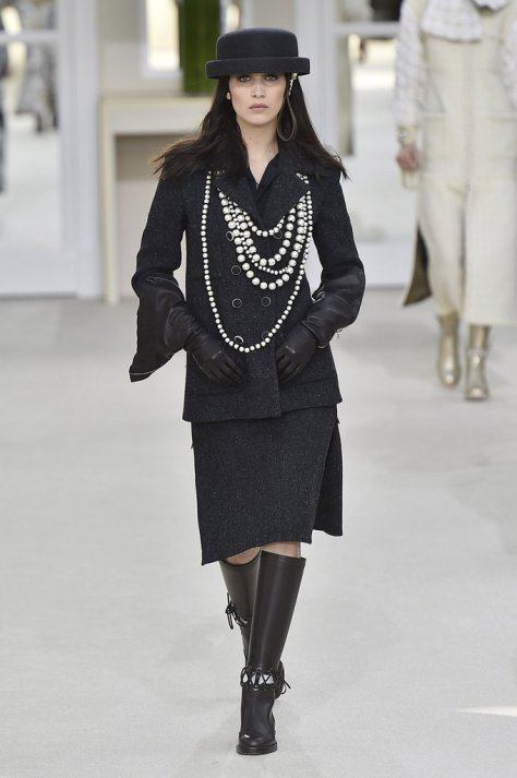 Bella looked like a modern-day Coco Chanel on the runway in her layers of pearls, crisp hat, and tailored separates. She finished her outfit with leather gloves and knee-high boots.