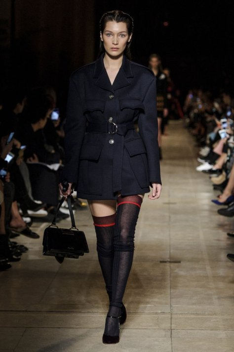 Bella walked down the Miu Miu runway in a structured jacket and sheer knee-high socks. Her look got a feminine touch from ankle-strap pumps, and she held onto a square belted satchel.