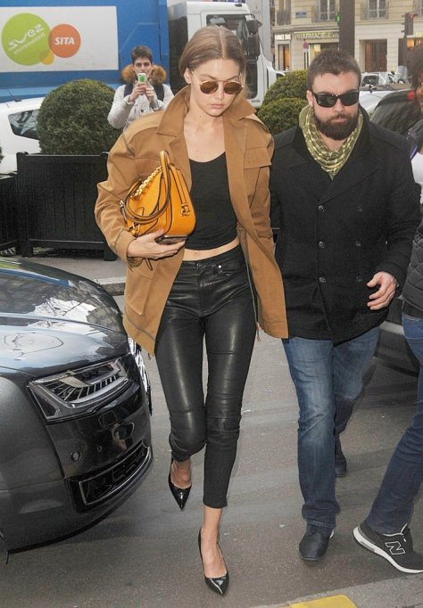 Gigi followed close behind Bella, clutching her own Miu Miu bag and playing up a trench with leather skinnies and heels. She finished her look with Krewe du Optic sunglasses.