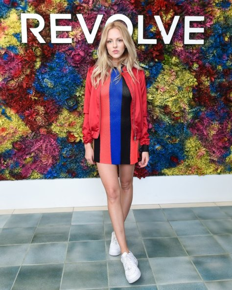 Shea Marie wearing a striped dress and bomber jacket at the Revolve festival.