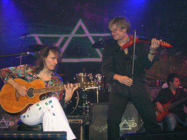 Steve Vai and Alex DePue on stage performing, Vai seated with acoustic guitar, Alex standing with elec. Viper violin.