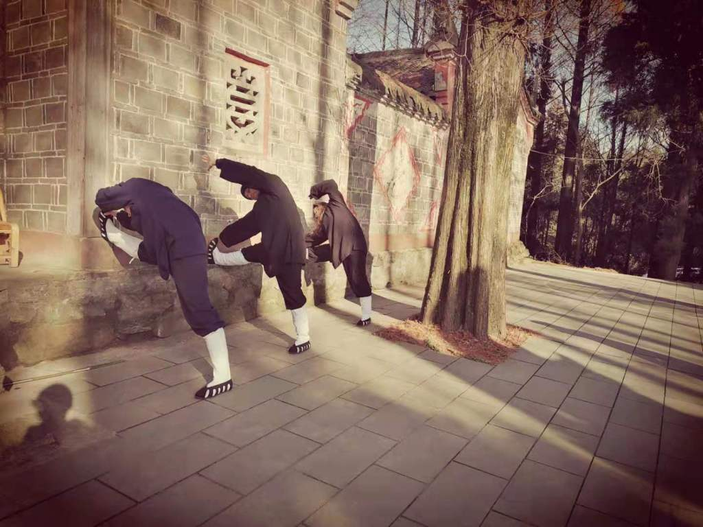 Students from the Five Immortals temple who are stretching