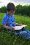 boy reading outside