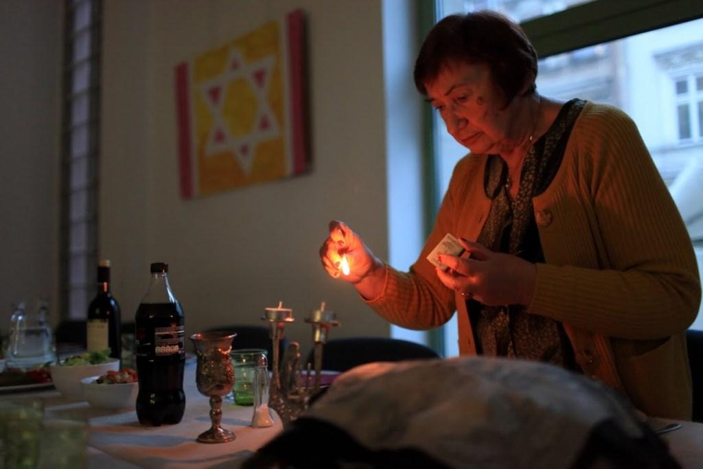Holocaust survivor Zofia lights shabbat (sabbath) candles. Photo: JCC