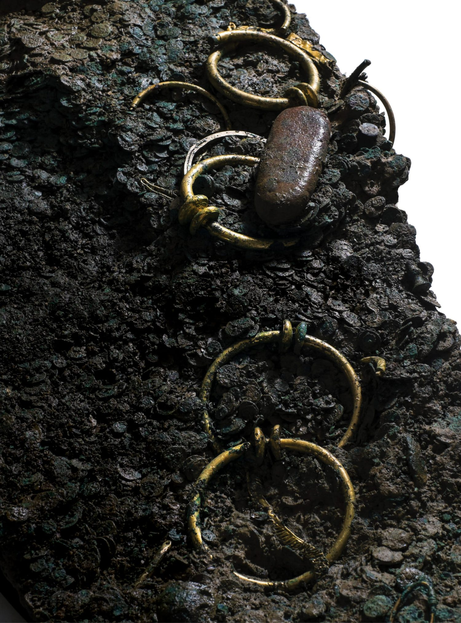 Above This photo shows just a portion of Le Câtillon II, the largest coin hoard yet found in the British Isles, which was discovered in Jersey in 2012. As well as more than 69,000 Celtic coins, the corroded mass included gold and silver objects, traces of textiles, and other intriguing artefacts.