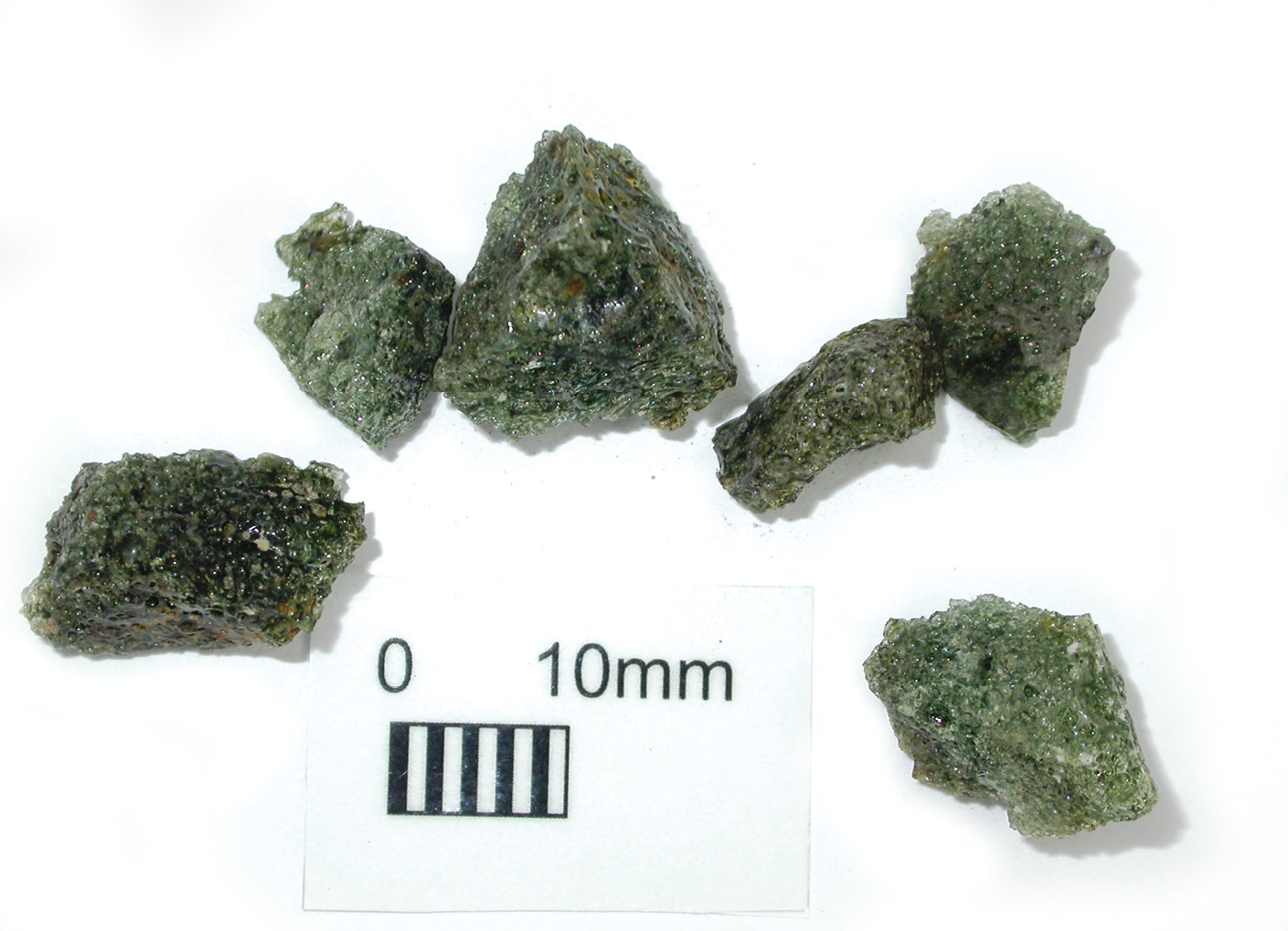 LEFT The most-common defects in early glass were bubbles and 'stones' usually in the form of sand particles that had not melted fully or, as here, fragments of crucible or furnace roof that dropped into the molten glass during firing. This example, from a furnace site at Glasshouse Lane, Kirdford, West Sussex, had been pulled out of the molten glass by the glass-blower using tongs and thrown on a waste pile. ABOVE Various methods were used to drive bubbles out of the molten glass, including the introduction of organic materials (a potato was sometimes used) to create large gas bubbles that would sweep up the small ones (called 'seed') as they rose to the surface in a 'violent ebullition of the whole mass'. Reaching the surface, the bubbles often overflowed the rim of the crucible to produce 'frothy' glass waste, like these finds from Silkstone, South Yorkshire.