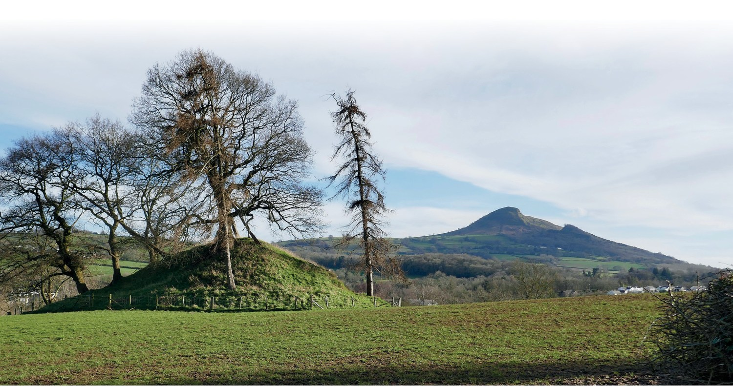 above The motte at Tre-fedw (shown here with the distinctive ridge of Skirrid Hill in the background) was one of a chain of six castles spaced at intervals of 1.5 miles, built to define the boundary between the March of Ewyas and the Kingdom of Gwent.