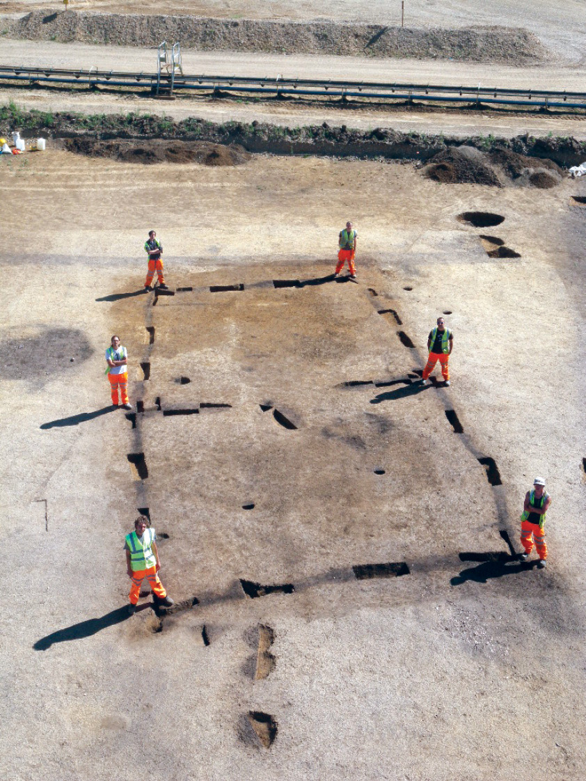 RIGHT The footprint of the original house measured 15m by 7.5m, but this substantial structure seems to have been built around just six post-holes (each marked here by a member of Wessex Archaeology).