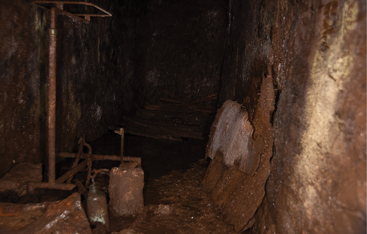 LEFT A narrow passage at the rear of the field dressing station appears to have served as a surgery. A surgical stand and leg brace are still present, while stretcher beds lie at the far end (Below).
