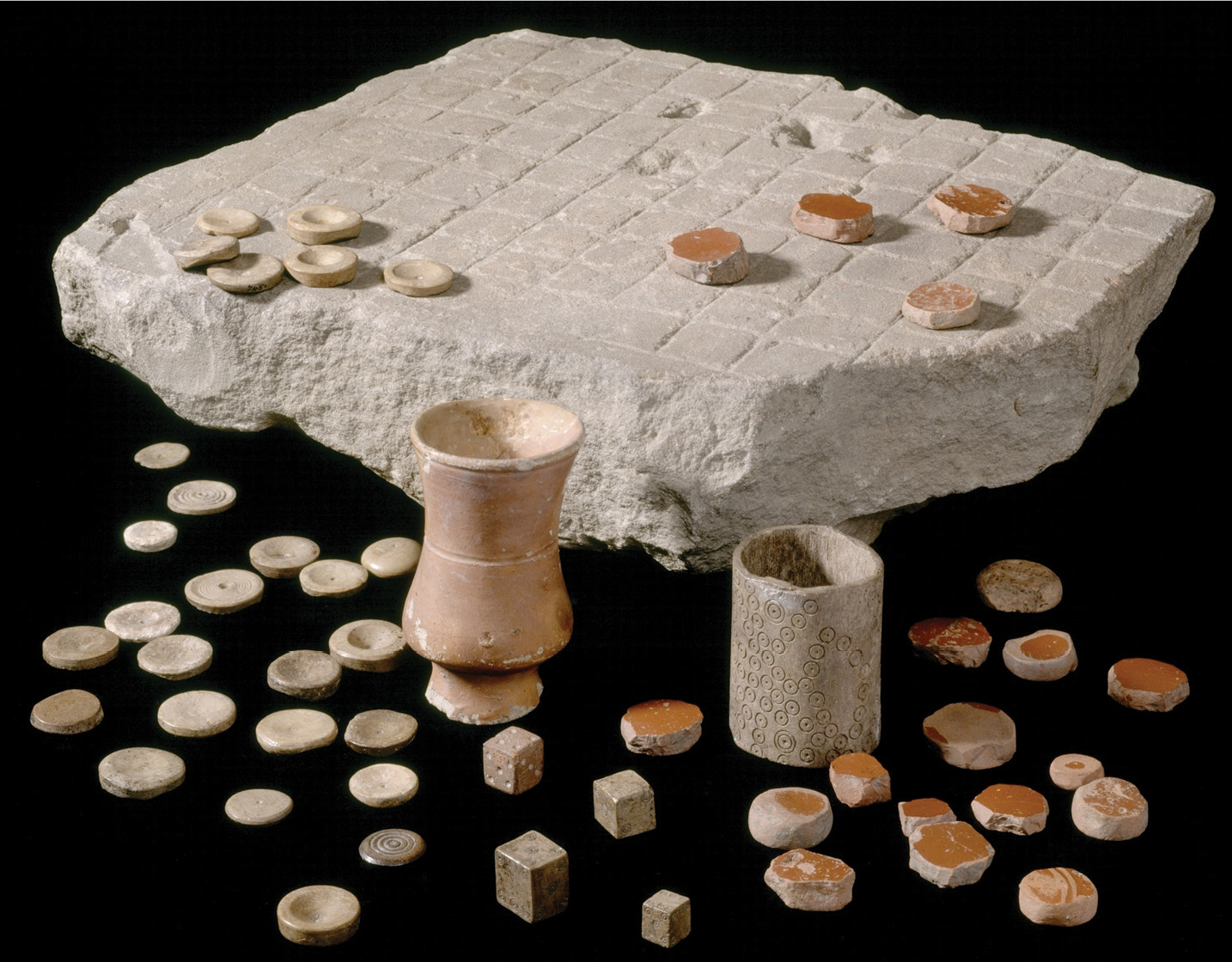 left A stone-carved gaming board from Corbridge with four bone dice, bone counters, counters cut down from Samian vessels, and two shakers, one of bone and one of ceramic.