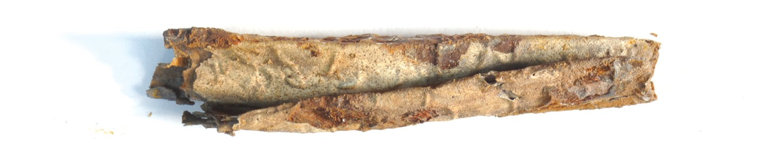 BELOW At the bottom of the photograph is a lead container that encased a silver scroll (shown at the top). This scroll was unfolded digitally to reveal 17 rows of pseudo-Arabic letters, which do not have a coherent meaning, but belong to the Graeco-Roman tradition of magical texts.